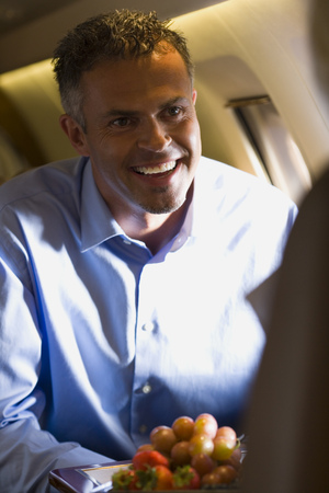 A Businessman Smiling In An Airplane