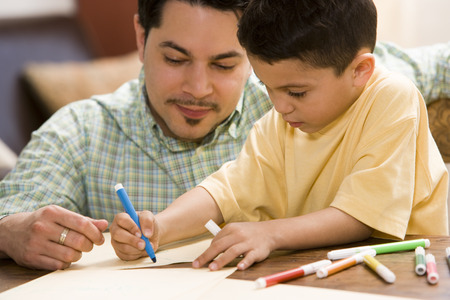 Young Boy Coloring And Drawing With Father Supervising LANG_EVOIMAGES