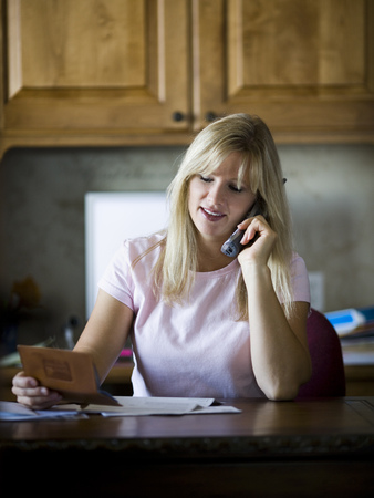Woman Paying Bills Over Telephone LANG_EVOIMAGES