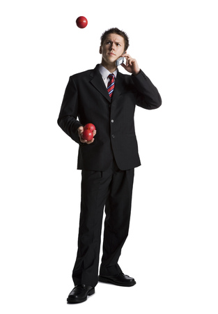 Businessman Juggling While Talking On Phone