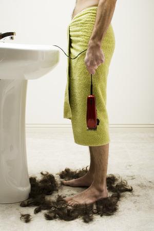 Man In Bath Towel Standing In Hair With Razor At Bathroom Sink