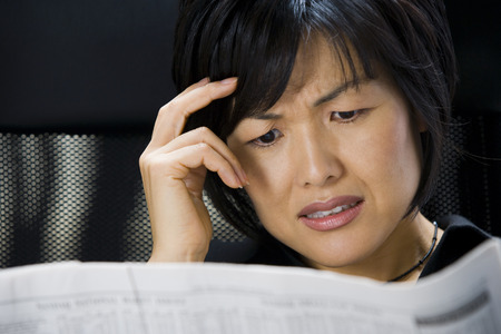 Woman Reading Financial Pages Of Newspaper