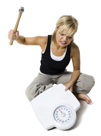 cross legs: Frustrated Dieting Woman Smashing Bathroom Scale With A Hammer