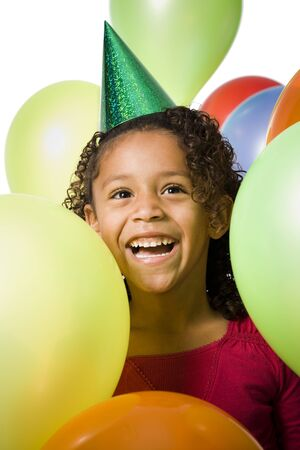 kids birthday party: Young Girl Wearing Party Hat And Playing Amongst Balloons