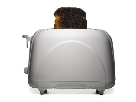 burned out: Slice Of Burnt Toast In A Toaster