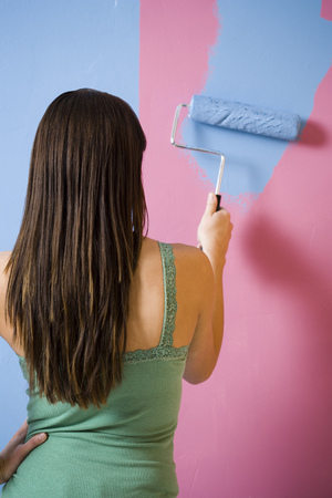 Rear View Of Woman Painting Wall With A Paint Roller