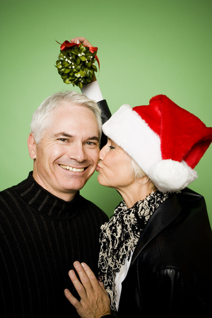 aging woman: A Woman Holds Mistletoe Over A ManS Head While Kissing Him On The Cheek