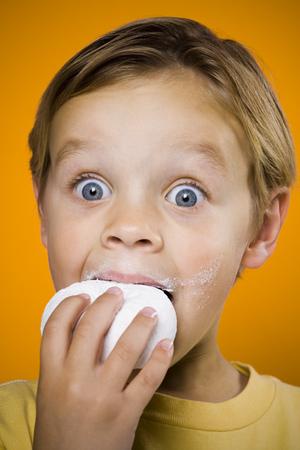Boy With Blue Eyes Eating Donut LANG_EVOIMAGES