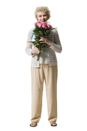 aging woman: Older Woman With A Bouquet Of Pink Roses