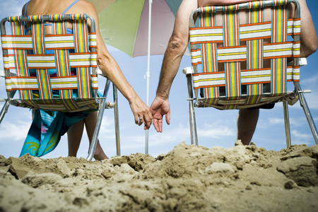 Mature Couple At The Beach Relaxing On Deck Chairs