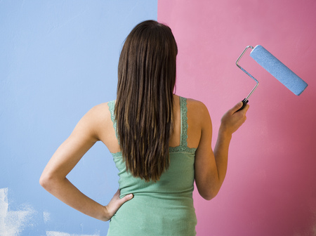 alteration: Rear View Of Woman Painting Wall With A Paint Roller