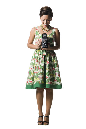 Woman In Floral Dress Holding Antique Camera LANG_EVOIMAGES
