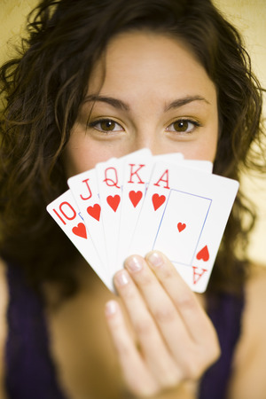 Teenage Girl Playing Poker Holding Straight Flush LANG_EVOIMAGES