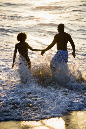 african american woman silhouette: Couple Walking Hand In Hand On Beach