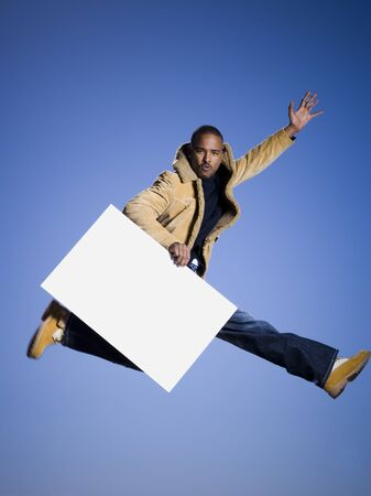 move in: African American Man Jumping And Holding A Blank Sign LANG_EVOIMAGES