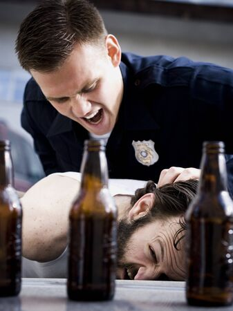 Police Officer Arresting Man Lying Down With Beer Bottles LANG_EVOIMAGES