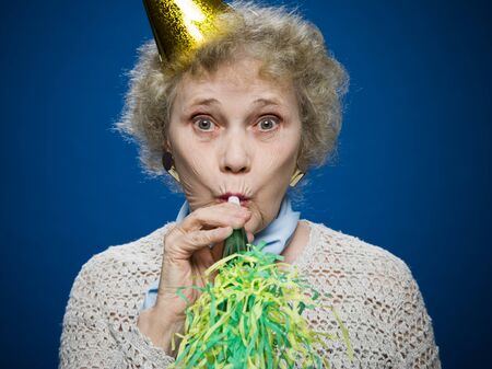 aging woman: Older Woman Wearing A Party Hat Blows A Noisemaker