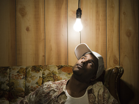 Man Sitting On Sofa Looking Up At Light Bulb