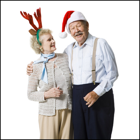 aging woman: An Elderly Couple Wearing Christmas Hats Laugh Together