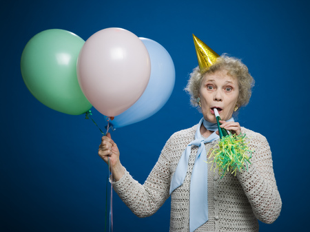 aging woman: Older Woman With Noisemaker And Party Hat