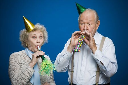 aging woman: Older Couple With Noisemakers And Party Hats