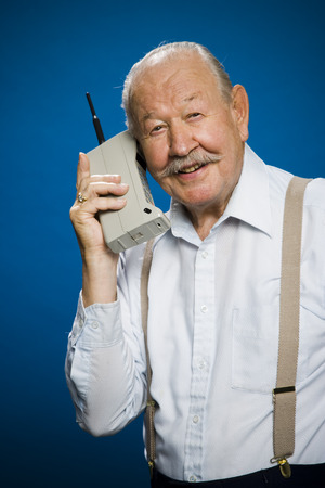 aging face: Older Man Making Call On Retro Wireless Phone