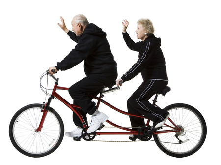 aging woman: Older Couple Riding A Tandem Bicycle