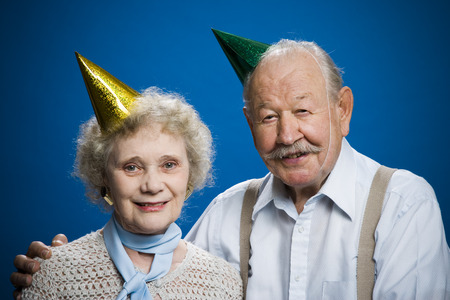aging woman: Older Couple Wearing Party Hats