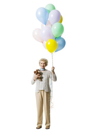 aging woman: Older Woman Holding Balloons