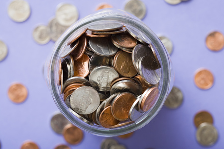 Glass Jar With Coins And Scattered Coins