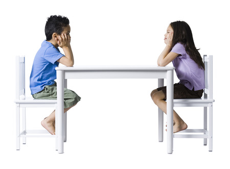 Boy And Girl Sitting At Table With Hands On Faces