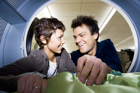 dryer: Couple Smiling At Dryer In Laundromat With Clothing