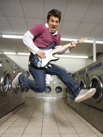 dryer: Man Playing Electric Guitar At Laundromat LANG_EVOIMAGES