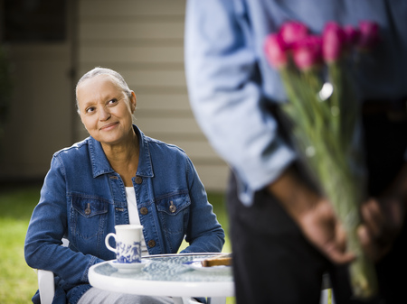 aging woman: Mature Woman Sitting Outdoors Smiling With Man Concealing Flowers LANG_EVOIMAGES