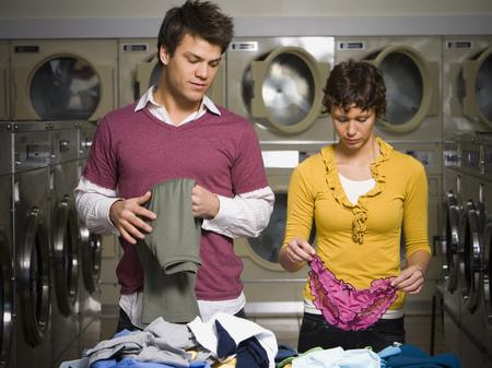 dryer: Couple Folding Laundry In Laundromat
