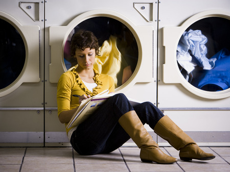 dryer: Woman Sitting At Laundromat With Books Writing