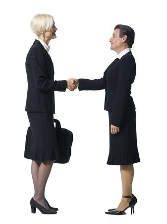 Empresaria madura estrechándole la mano con la cabeza de la empresaria con el hombre