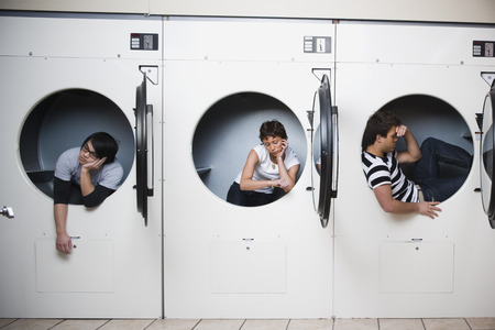 dryer: Three People In Dryers At Laundromat Waiting