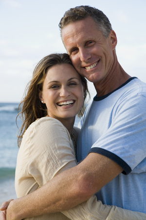 Man And Woman Hugging Outdoors On Beach Smiling