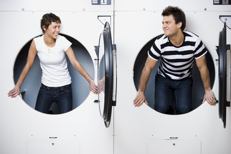dryer: Man And Woman In Laundromat Dryers Smiling