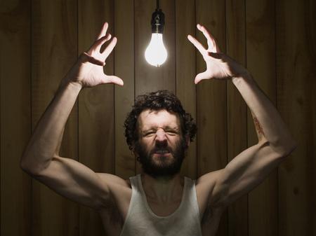 Man Reaching To Light Bulb Gritting Teeth