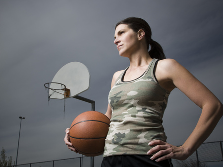 Woman Holding Basketball With Net In Background LANG_EVOIMAGES