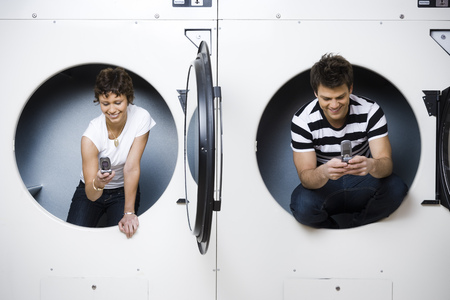 dryer: Two People In Dryers At Laundromat With Cell Phones