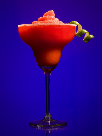 release: Red Slush Beverage In Cocktail Glass With Lime Garnish LANG_EVOIMAGES