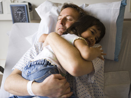 Male Patient In Hospital Hugging Young Girl LANG_EVOIMAGES