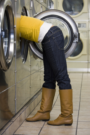 dryer: Side Profile Of Woman With Head And Arms In Dryer At Laundromat LANG_EVOIMAGES