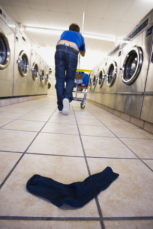 dryer: One Sock On Floor At Laundromat With Man And Trolley