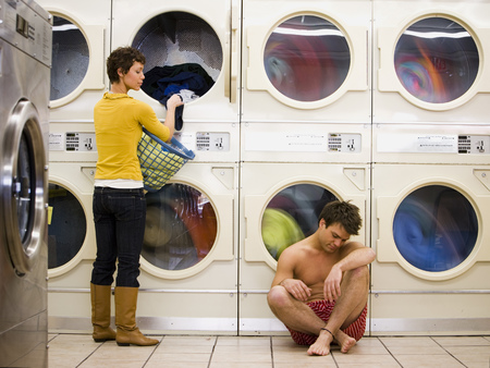 dryer: Man In Boxers Sleeping At Laundromat With Woman Removing Clothing From Dryer