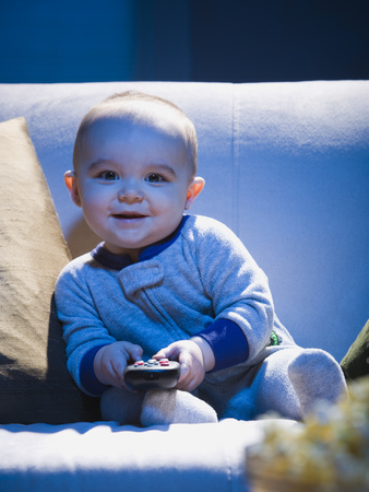 Baby On Sofa With Television Remote Smiling