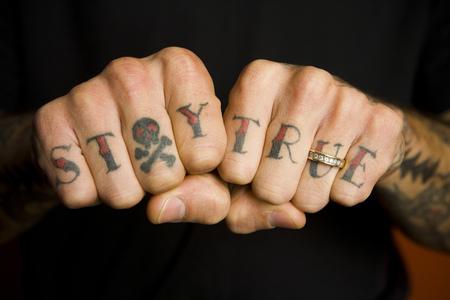 puños cerrados: Vista detallada de las manos con la certeza en los dedos y la banda de boda
